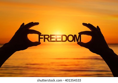 Silhouette, Close up Hand holding FREEDOM text with blurred sea sunset. sunlight effect.