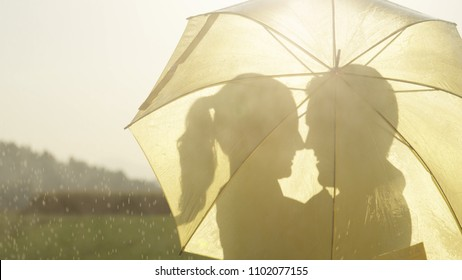 SILHOUETTE CLOSE UP LENS FLARE: Man and woman in love hide behind umbrella as they are about to kiss in the golden countryside. Cheerful young couple dancing in the rain stops and gazes at each other.