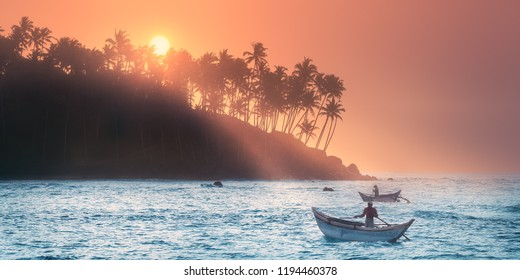 Silhouette of coconut palm, fishermen and sunbeams true trees on beach at sunrise Mirissa, Sri Lanka. Clipping path of sky