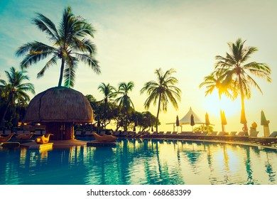 Silhouette coconut palm tree around swimming pool in hotel and resort at sunrise time - Vintage Filter