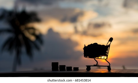 Silhouette coin in the shopping cart and coin in stack with sunset in financial money concept with coconut tree