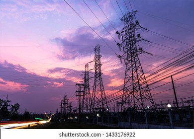 Silhouette of columns and high voltage wires In the power supply station There is a twilight background and have many car traffic.