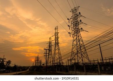 Silhouette of columns and high voltage wires In the power supply station There is a sunset background.