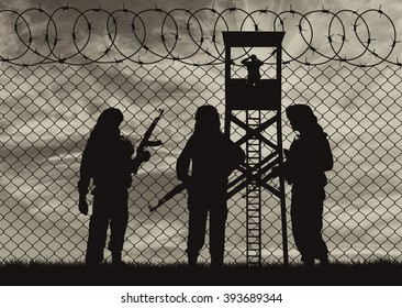 Silhouette Concept of terrorism. Silhouette terrorists near the border fence in the background at sunsetof soldier with a gun