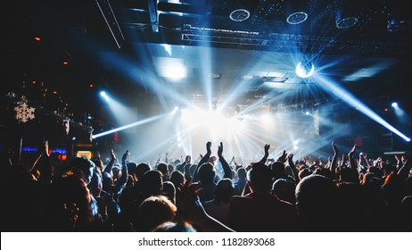 Photo of silhouette of concert crowd in front of bright stage lights. Dark background, smoke, concert  spotlights, disco ball