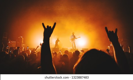 Silhouette of concert crowd in front of bright stage lights and guitar player / guitarist perform on concert stage. Dark background, smoke, spotlights