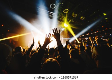 silhouette of concert crowd with hands up in front of bright stage lights.
