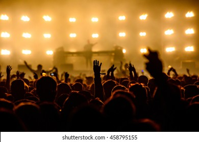 Silhouette Concert People in Crowd with hands up at a Music Festival - Backlit with Lighting.