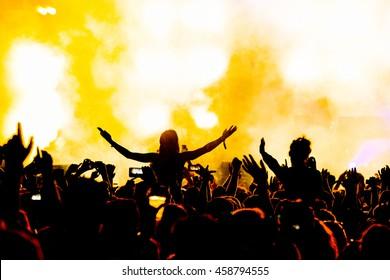 Silhouette Concert People on Shoulders in Crowd mit Händen oben bei einem Musikfestival - Backlit with Lighting.