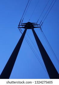 Silhouette of a concrete pylon with two piers in the blue hour.