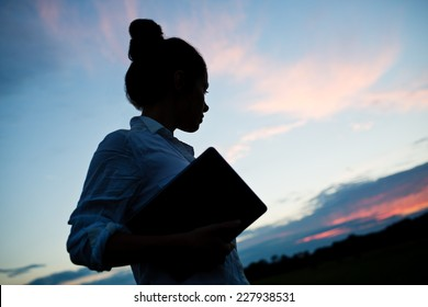 Silhouette of confident business woman holding tablet outside in front of blue sky. Dramatic photo with atmospheric sunset light. Woman looking to the future.