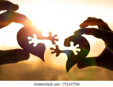 silhouette connect heart two pieces of puzzle in hands of lovers against the background of sunrise. Valentine's Day,