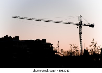 Silhouette of a construction crane against the sky.