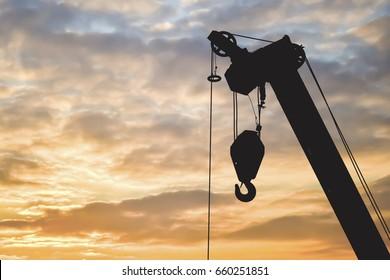 Silhouette construction crane on sunset sky