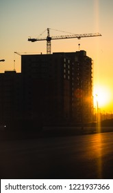 Silhouette of construction cranes over new residential buildings at sunset. Urban background