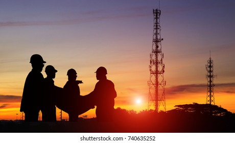 Silhouette construction engineer standing orders for worker team looking Telecommunication mast television at sunset, Teamwork concept