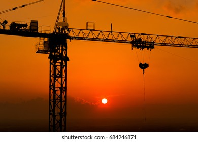 Silhouette construction site crane on sky background, sunset time