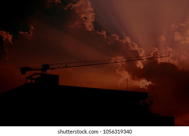 Silhouette of construction site over sun ray with cloud. Concept of industry background.
