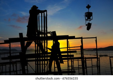 silhouette construction team working on sunset time