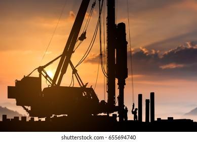 silhouette construction worker concrete construction pile driving in construction site,civil construction engineer driving pile during sunset time