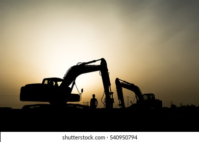 silhouette of a construction worker and  excavator in oilfield.