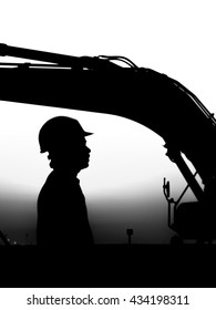 silhouette of a construction worker in oilfield with excavator at background- black and white