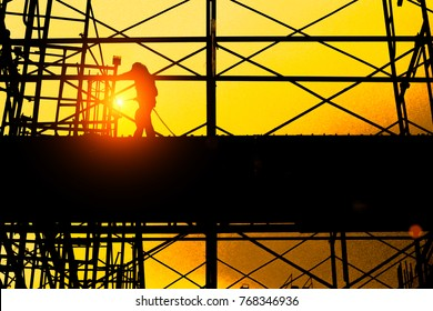 silhouette of construction worker construction worker on construction site , industry background