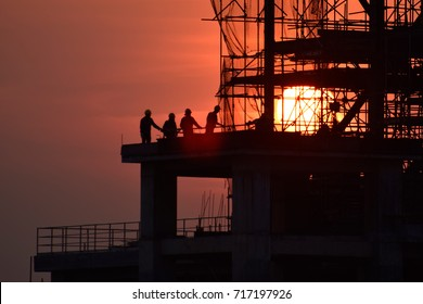 Silhouette construction worker , tower cranes build large residential buildings  at construction site industry .