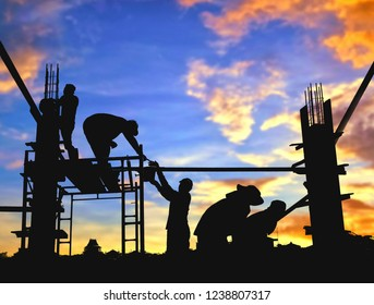 Silhouette construction workers group are pouring concrete on top of building with blurred  colorful sunrise sky background in construction concept