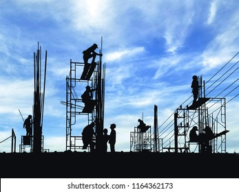 Silhouette construction workers group are working to build reinforcement structure on top of building with blurred clouds and blue sky background in construction site, industrial concept