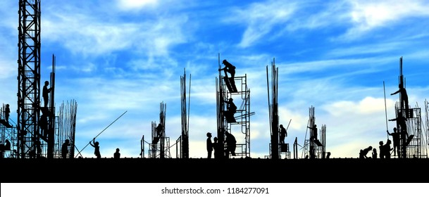 Silhouette construction workers group are working to build reinforcement structure on top of building in construction site with blurred clouds and blue sky background, panorama view