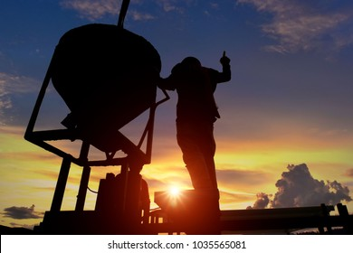 The silhouette of the construction workers in the construction site is very beautiful sunset.