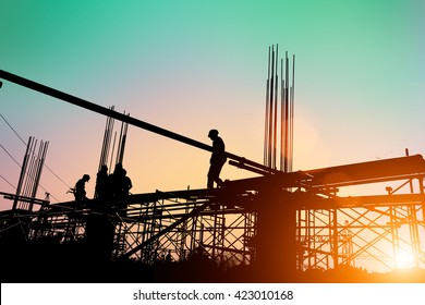 Silhouette of construction workers working on scaffolding at a high level by the standards set must include a safety belt  Heavy industry concept.