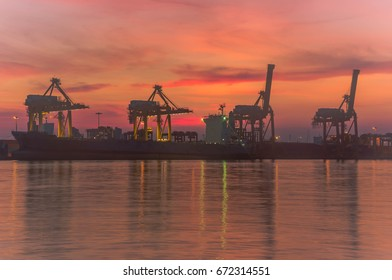 Silhouette container cargo freight ship with working crane bridge in shipyard with sunrise twilight colorful sky for Logistic Import Export background