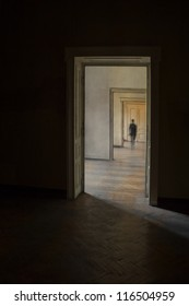 Silhouette in a corridor in front of a closed door. Rite of passage concept. Linear perspective view through several open doors and empty rooms.