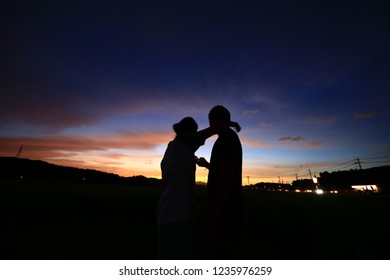 The silhouette of a couple against magic hour sky