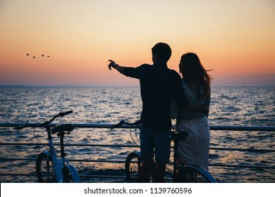 Silhouette of a couple with bikes at the beach at sunrise sky summer time, seashore summer beach at yellow blue evening horizon sea, sunset background