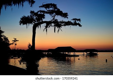 Silhouette of a couple of boathouses and trees over the lake at sunset with beautiful blue and orange sky.