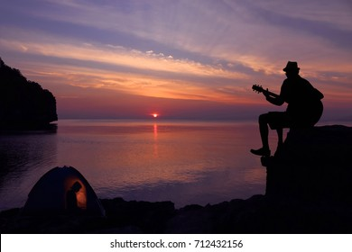 Silhouette couple camping and playing a guitar on the beach with sunset sky background.