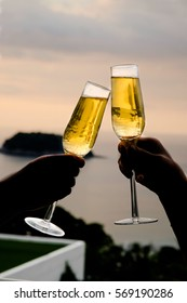 Silhouette of couple drinking champagne at sunset sky for a beautiful background. Christmas festive celebration. End of the year Welcome to New Year 2020.