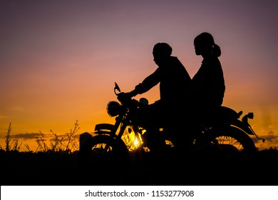 Silhouette of couple driving a motorcycle on street, enjoying freedom and active lifestyle, having fun on a bikers tour on sunset background.