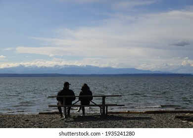 Silhouette of a couple enjoying the afternoon on a calm and peaceful relaxing in front of the ocean view.