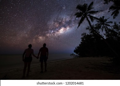 Silhouette of couple gazing and enjoying the view of milky way on the beach of Zanzibar with palm trees in background. Tanzania