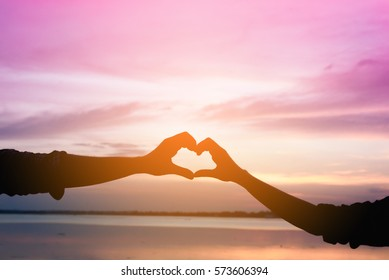 Silhouette of couple hand attached to heart shape at the sunset. Abstract of emotional love, Love and Valentine's day concept.