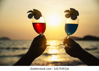 Silhouette couple hand holding cocktail glass decoration with plumeria flower with beach background - happy relax celebration vacation in sea nature concept