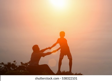 silhouette of couple help each other trust assistance in sunset