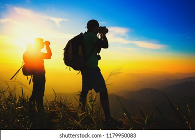 silhouette couple hiker watching through binoculars on the top of mountain