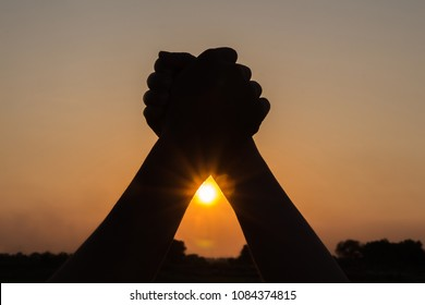 silhouette of couple holding hands up celebrating victory beautiful sunset background,people winning concept
