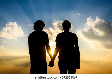 Silhouette of Couple Holding Hands at Sunset with sunrays background