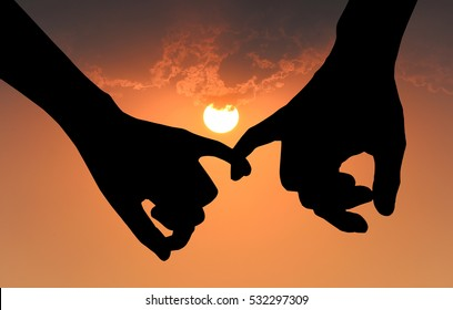 Silhouette of couple hooking each other's little finger on sunset background, hand in hand